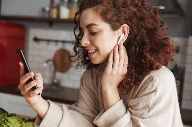 Portret van een schattige europese vrouw met oordopjes die naar muziek luistert op de mobiele telefoon tijdens het koken in het keukeninterieur thuis
