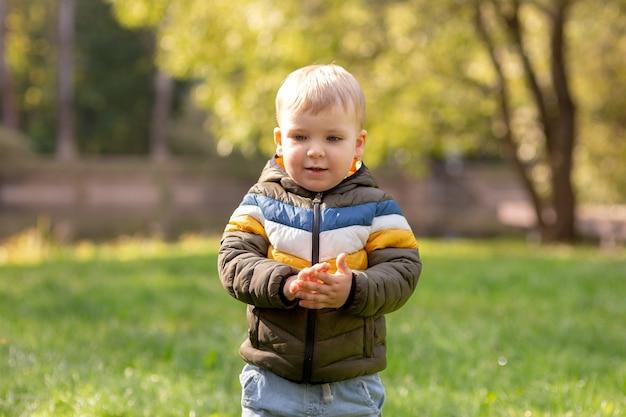 Portret van een schattige glimlachende kleine blonde jongen in een jas op een groen gazon in het park. kopieer ruimte.