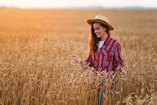 Portret van een schattige jonge, gelukkig lachende boer die alleen staat tijdens het wandelen door een geel veld van droge rijpe tarwe tussen gouden aartjes bij zonsondergang