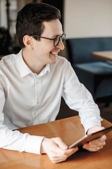 Portret van een schattige jonge man zittend op tafel met behulp van een tablet wegkijken lachen bril dragen.