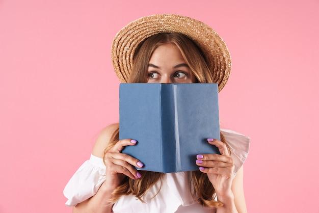 Portret van een schattige jonge mooie vrouw die zich voordeed over een roze muur met een boek dat haar gezicht bedekt.