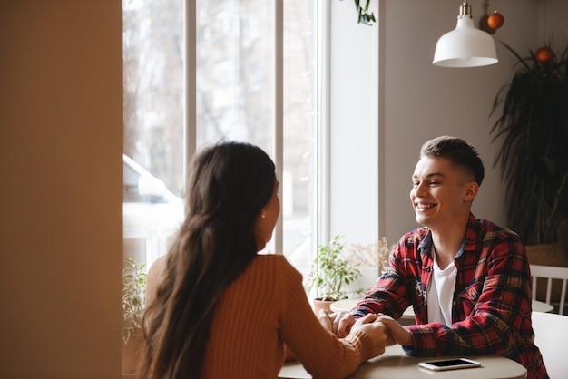 Portret van een schattige jonge verliefde paar zitten in café binnenshuis hand in hand van elkaar.