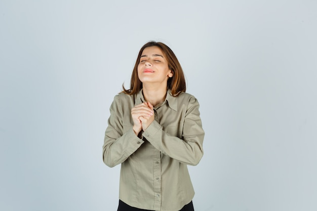 Portret van een schattige jonge vrouw die de handen over de borst klemt in een biddend gebaar in het hemd en er dankbaar vooraanzicht uitziet