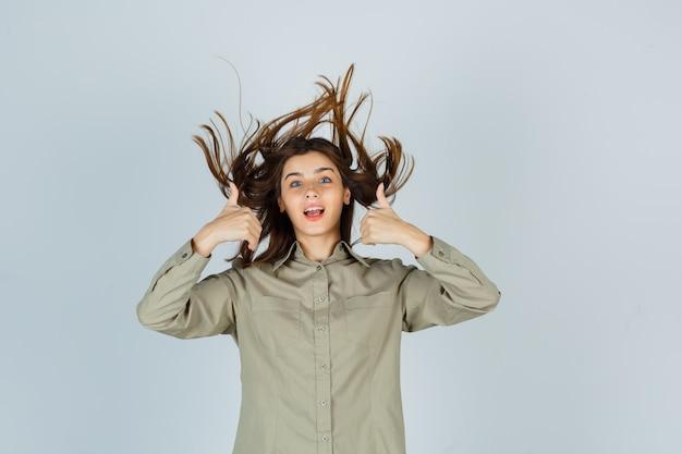 Portret van een schattige jonge vrouw die dubbele duimen omhoog laat zien terwijl ze poseert met vliegend haar in shirt en er een gelukzalig vooraanzicht uitziet