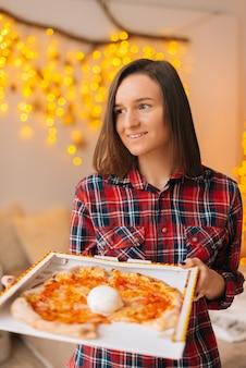 Portret van een schattige jonge vrouw die een doos pizza vasthoudt.