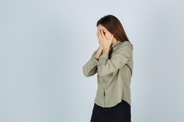 Portret van een schattige jonge vrouw die het gezicht bedekt met de handen in het hemd, de rok en een depressief vooraanzicht kijkt