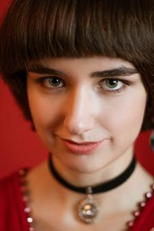 Portret van een schattige jonge vrouw met kort haar, close-up op een rode achtergrond. kijkend naar de camera, verticale foto