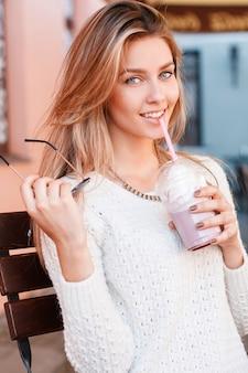Portret van een schattige jonge vrouw met mooie blauwe ogen met een lieve glimlach met blond haar in een gebreide vintage trui met een milkshake in handen. geweldig meisje geniet van de vakantie