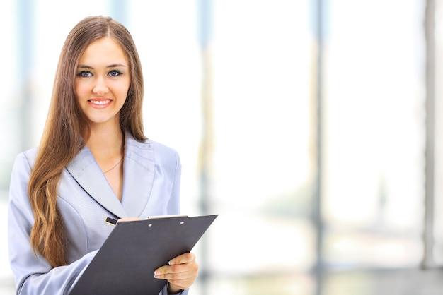Portret van een schattige jonge zakenvrouw die lacht in een kantooromgeving