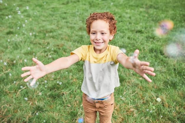 Portret van een schattige jongen die buiten in het park met bubbels speelt en een glimlach kopieert