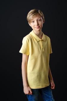 Portret van een schattige jongen in een geel t-shirt op een zwarte achtergrond poseren voor de camera