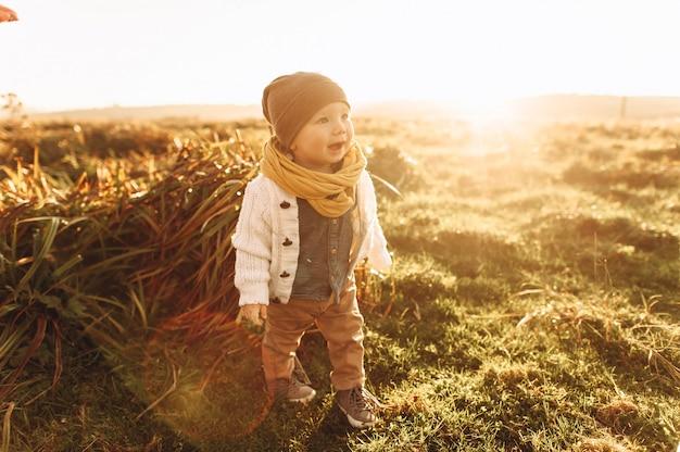 Portret van een schattige jongen loopt door het veld bij zonsondergang
