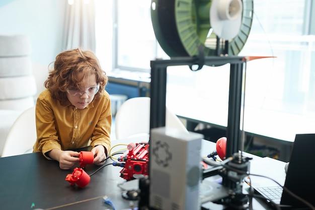 Portret van een schattige jongen met krullend haar die een robotboot bouwt tijdens de techniekles op de moderne school, kopieer ruimte