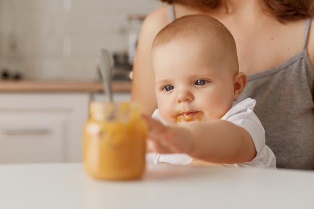 Portret van een schattige kleine baby die op moederknieën zit en een lepel probeert te nemen met groente- of fruitpuree, nieuwsgierige baby die de wereld bestudeert, aanvullende voeding.