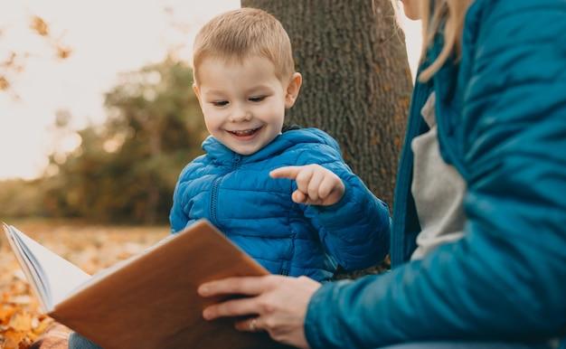 Portret van een schattige kleine jongen die een boek buiten leest met zijn moeder lachend.