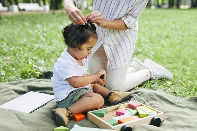 Portret van een schattige kleine jongen die met speelgoed in het park speelt terwijl hij op groen gras zit en geniet van de zomer...