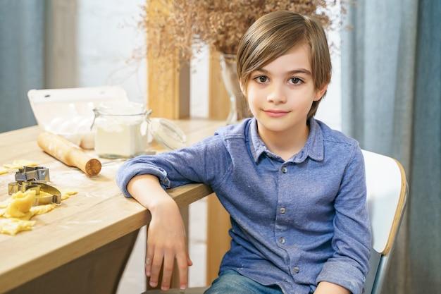 Portret van een schattige kleine jongen die zelfgemaakte koekjes in de keuken kookt.
