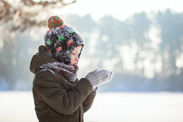 Portret van een schattige kleine jongen in warme kleding buiten blazen op sneeuw tijdens sneeuwval in zonnige winterdag.