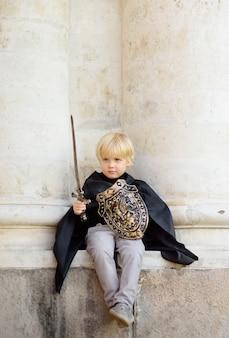 Portret van een schattige kleine jongen verkleed als een middeleeuwse ridder