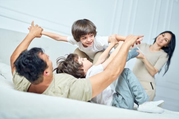 Portret van een schattige kleine latijnse jongen die plezier heeft, speelt met zijn ouders en broer of zus, die thuis samen op een bed ligt. gelukkige jeugd, ouderschapsconcept
