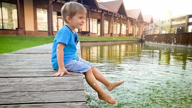 Portret van een schattige lachende peuterjongen die aan de rivier in een klein stadje zit en zijn voeten in het water houdt
