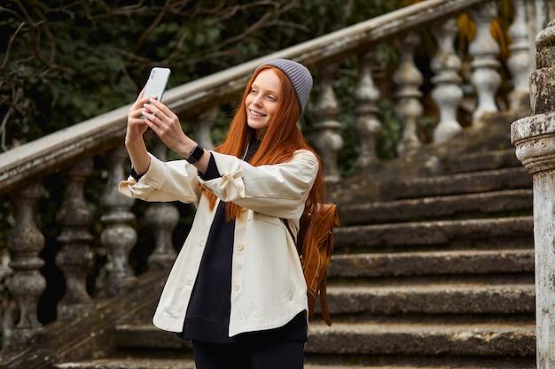 Portret van een schattige moderne vrouw die een selfie-foto neemt op de achtergrond van het bouwen van historische trappen en...