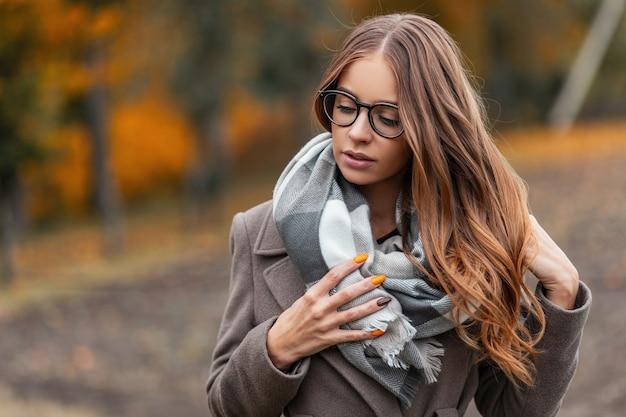 Portret van een schattige mooie jonge vrouw in modieuze bril met lang bruin haar in een gebreide sjaal in een stijlvolle jas. aantrekkelijk meisje maakt kapsel recht en kijkt naar beneden. casual herfstlook.