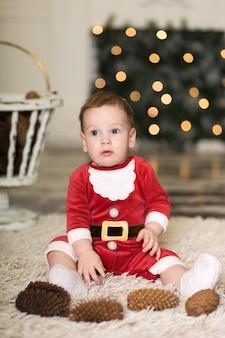 Portret van een schattige peuter die op de vloer speelt met kegels om de kerstboom te versieren, in de buurt van de kerstboom en dozen met kerstcadeaus, prettige kerstdagen en een fijne vakantie,