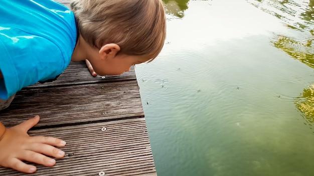 Portret van een schattige peuterjongen die op het oppervlak van het meer kijkt en kijkt naar veel waterstriders die drijven