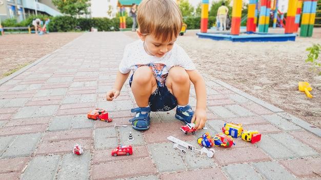 Portret van een schattige peuterjongen die speelt met veel kleurrijk speelgoed op de kindergrond