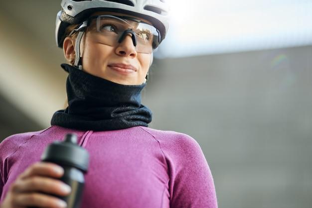 Portret van een schattige professionele vrouwelijke wielrenner met een roze pak en een nekwarmer die wegkijkt terwijl hij vasthoudt