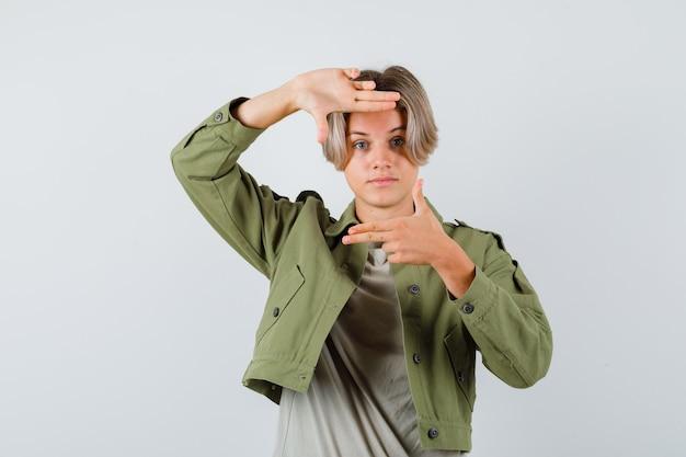 Portret van een schattige tienerjongen die een framegebaar toont met vingergeweren in een groen jasje en er zelfverzekerd uitziet
