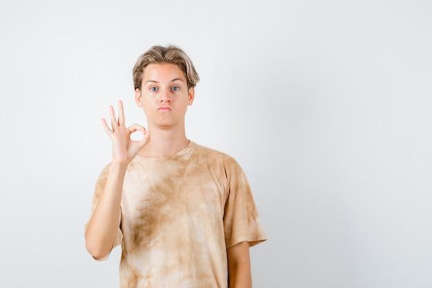 Portret van een schattige tienerjongen die een goed gebaar in een t-shirt laat zien en er verward vooraanzicht uitziet