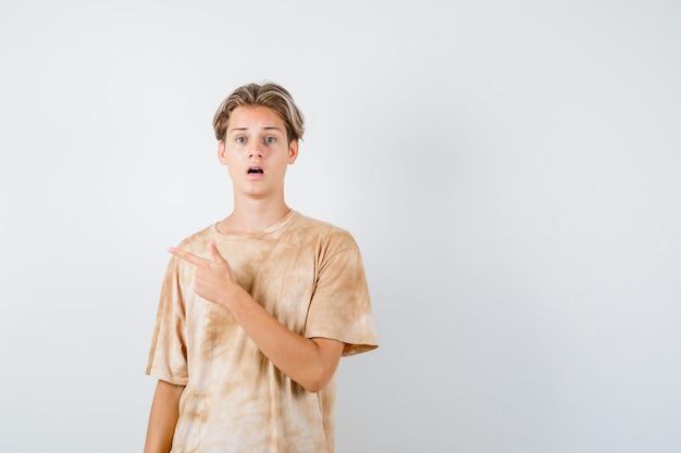 Portret van een schattige tienerjongen die naar de linkerbovenhoek in een t-shirt wijst en een verbaasd vooraanzicht kijkt