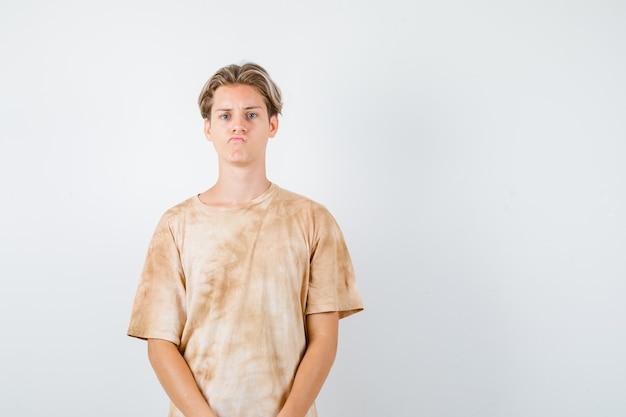 Portret van een schattige tienerjongen die naar de voorkant in een t-shirt kijkt en een teleurgesteld vooraanzicht ziet