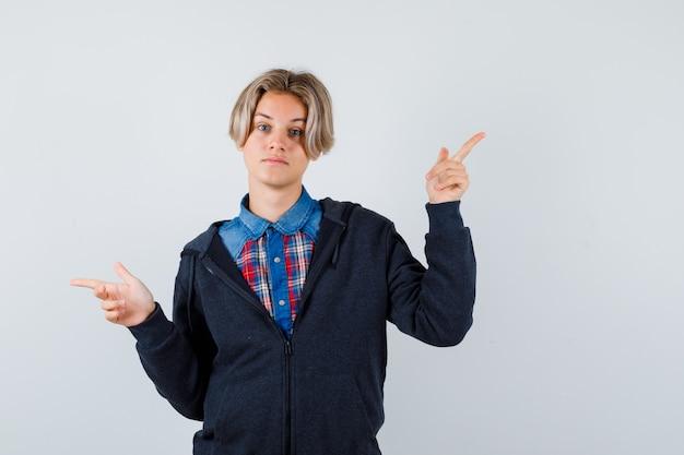 Portret van een schattige tienerjongen die naar rechts en links wijst in shirt, hoodie en peinzend vooraanzicht