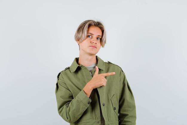 Portret van een schattige tienerjongen die naar rechts wijst, wegkijkt in een groene jas en aarzelend vooraanzicht kijkt