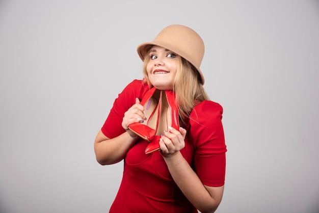 Portret van een schattige vrouw die een paar hakken vasthoudt.