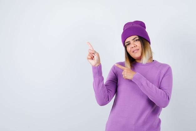 Portret van een schattige vrouw die naar de linkerbovenhoek wijst in een trui, muts en er vrolijk vooraanzicht uitziet