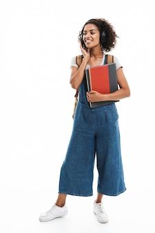Portret van een schattige vrouw die naar muziek luistert met een koptelefoon terwijl ze oefenboeken vasthoudt die over een witte muur zijn geïsoleerd