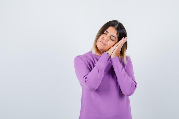 Portret van een schattige vrouw die op de handpalmen leunt als kussen in een paarse trui en er slaperig uitziet