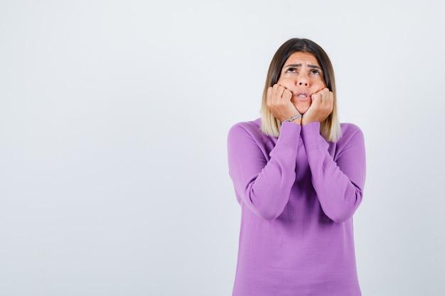 Portret van een schattige vrouw die wangen op handen leunt, omhoog kijkt in een paarse trui en opgewonden vooraanzicht kijkt