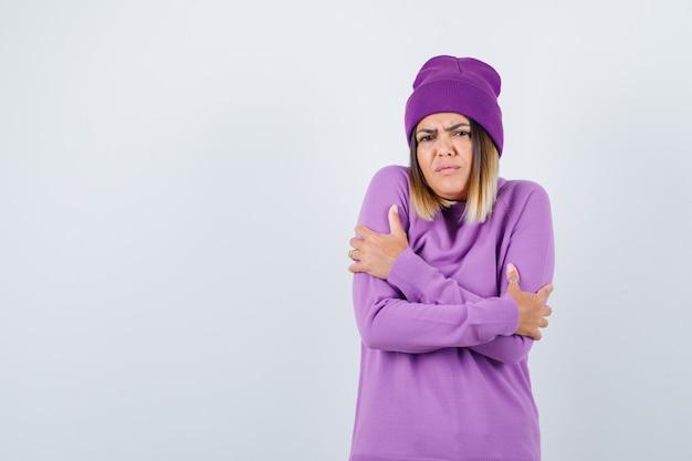 Portret van een schattige vrouw die zichzelf omhelst, het koud heeft in de trui, muts en er somber uitziet
