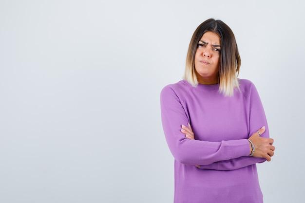 Portret van een schattige vrouw met armen gevouwen in paarse trui en peinzend vooraanzicht