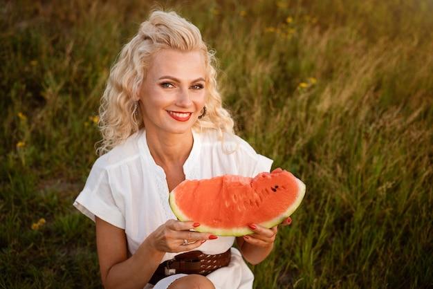 Portret van een schattige vrouw met een stuk watermeloen in haar hand in de natuur vrolijk meisje dat rijp eet...