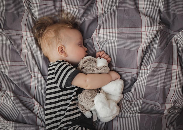 Portret van een schattige zes maanden oude blonde jongen slapen op een grijs bed met een stuk speelgoed in zijn handen