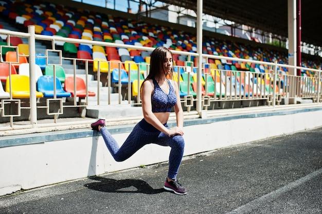 Portret van een schitterend meisje dat hurkzit in het stadion doet.
