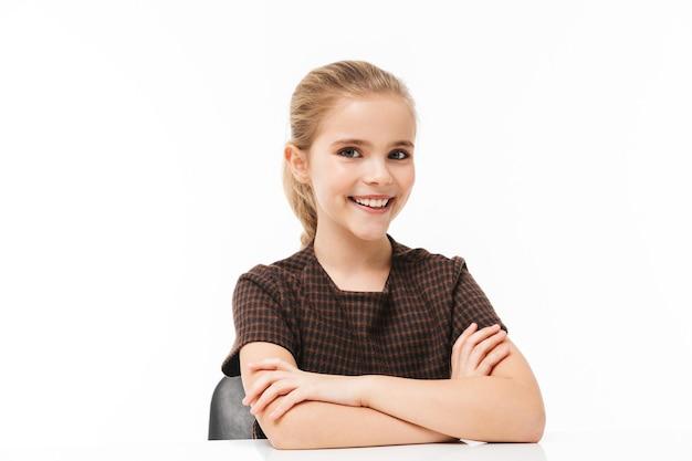 Portret van een schoolmeisje dat aan het bureau zit tijdens de les terwijl ze vakken studeert op school geïsoleerd over een witte muur