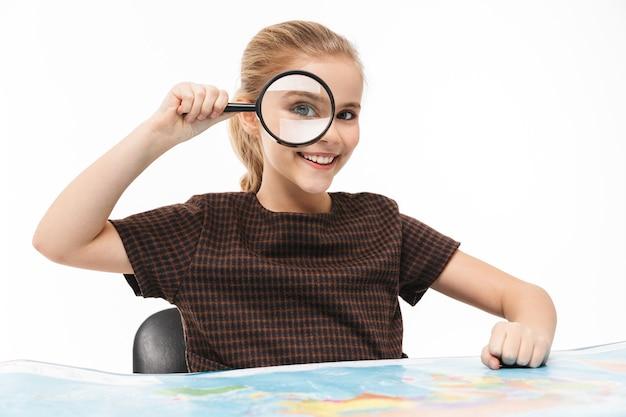 Portret van een schoolmeisje dat door een vergrootglas naar de wereldkaart kijkt terwijl ze aardrijkskunde studeert op school, geïsoleerd over een witte muur