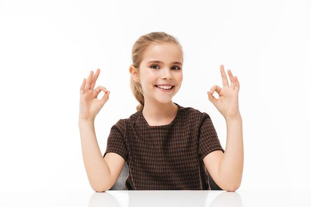 Portret van een schoolmeisje dat lacht en een goed teken toont terwijl ze aan het bureau zit in de klas geïsoleerd over een witte muur